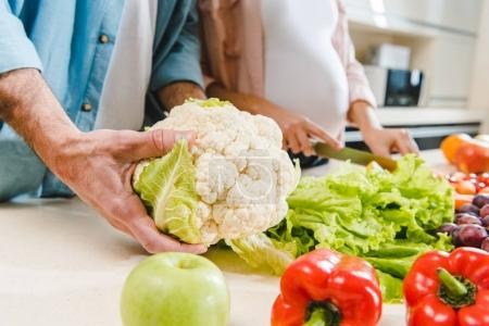 Photo for Cropped image of man and pregnant woman at kitchen with vegetables and fruits, hand holding cauliflower - Royalty Free Image