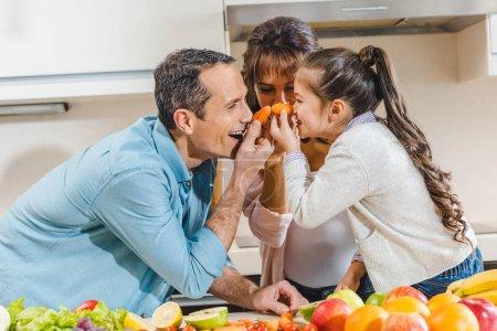Photo pour Famille heureuse à côté de la table avec des fruits et légumes applique peu de carottes au nez et en regardant les uns les autres à la cuisine - image libre de droit
