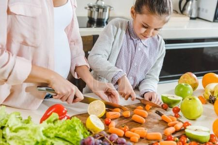 Photo for Partial view of mother with daughter slicing carrots on chopping board at kitchen - Royalty Free Image