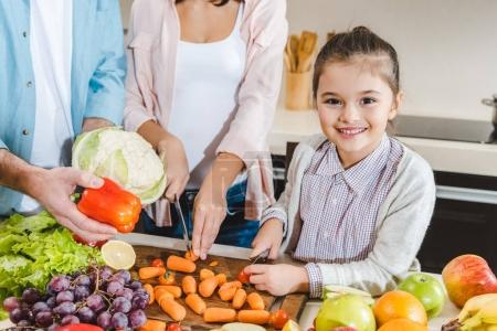 Photo for Cropped image of family at kitchen, little kid with mother slicing vegetables and looking at camera - Royalty Free Image