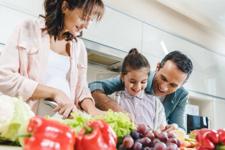 Photo for Cheerful family slicing fruits and vegetables together at kitchen - Royalty Free Image