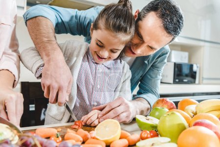 Photo for Happy father with daughter slicing vegetables and fruits on chopping board at kitchen - Royalty Free Image