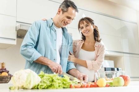 Photo for Happy pregnant couple making salad at kitchen - Royalty Free Image