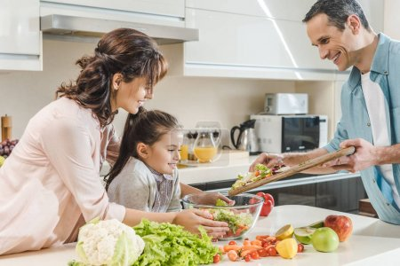 Photo for Happy smiling family making salad together at kitchen - Royalty Free Image