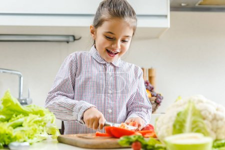 kid slicing pepper on chopping board