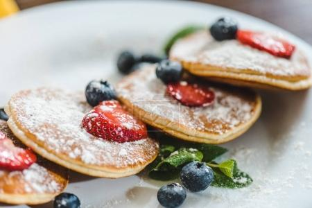 Photo for Closeup pancakes with berries and mint on white plate - Royalty Free Image