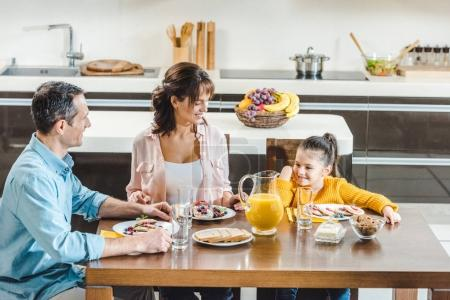 happy family sitting at table with juice and pancakes with berries at kitchen