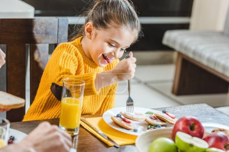 Photo for Little kid sitting at table and eating pancakes at kitchen - Royalty Free Image