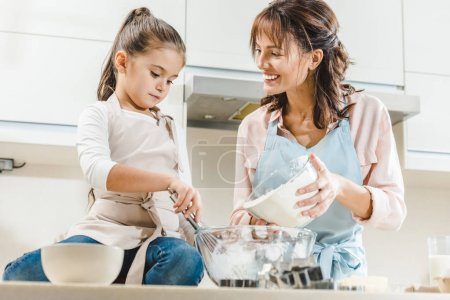 Photo for Happy mother with daughter making dough at kitchen - Royalty Free Image