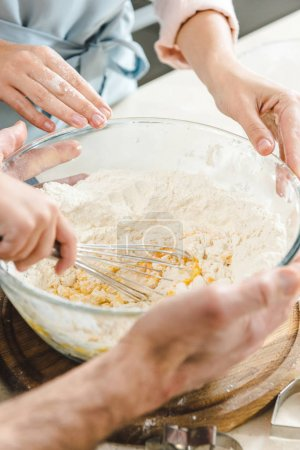 family hands mixing dough