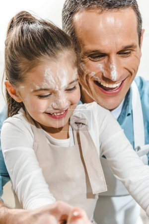 father and daughter with faces in flour
