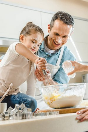 kid with father mixing dough