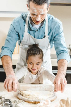 father with daughter rolling dough