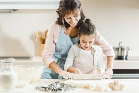 mother with daughter rolls out dough