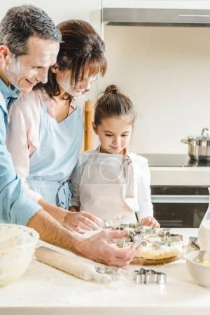 Photo for Happy caucasian family in flour making forms of dough at kitchen - Royalty Free Image