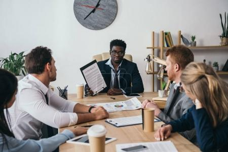 multiethnic group of businesspeople having conversation at office