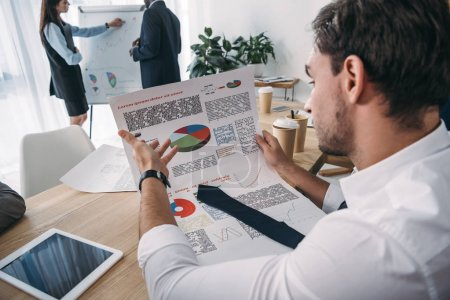 close-up shot of young handsome businessman discovering documents at office