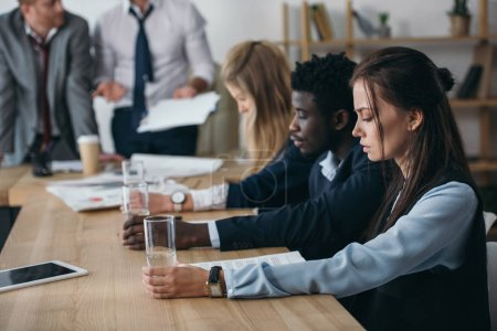 group of managers sitting with glasses of water in conference hall at office
