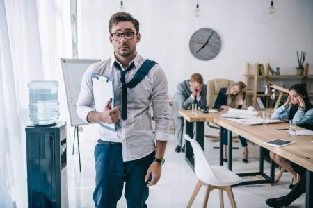 overworked untidy businessman with clipboard standing at office while colleagues sitting at conference hall
