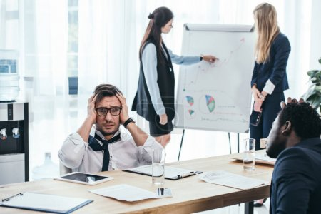 overworked businesspeople in conference hall at office