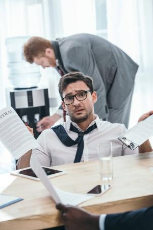exhausted businessman with paperwork sitting at office