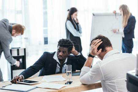 group of tired businesspeople in conference hall at office