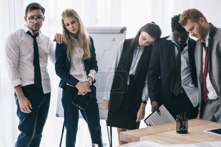 exhausted businesspeople sleeping while staning near whiteboard at office