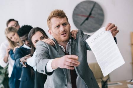 exhausted zombie like businesspeople standing in row and holding contract