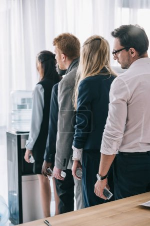 overworked managers standing in queue for water dispenser at office
