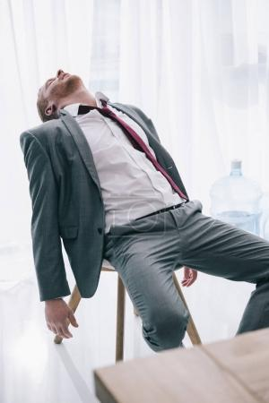 exhausted businessman sleeping on chair at office