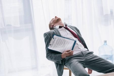 exhausted businessman sleeping on chair with contract in hand at office