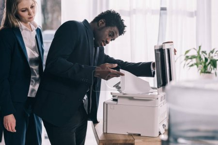 overworked african american manager using copier at office