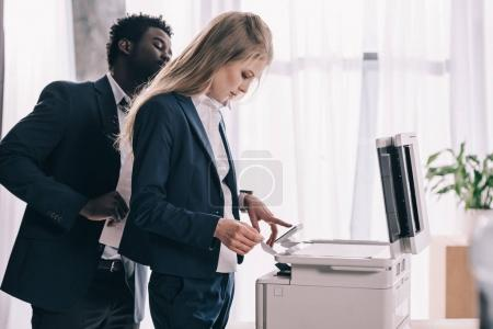 young businesspeople using copier together at office
