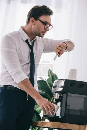 businessman pouring coffee from office machine and looking at watch