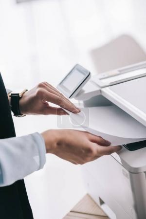 cropped shot of woman in formal wear using copier