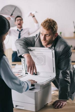 businessman helping colleague with copier at office