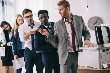 group of businesspeople standing in queue for copier at office