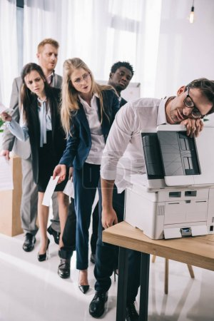 businessman sleeping on copier while his colleagues standing in queue behind him