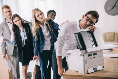 exhausted businessman sleeping on copier while his colleagues standing in queue behind him