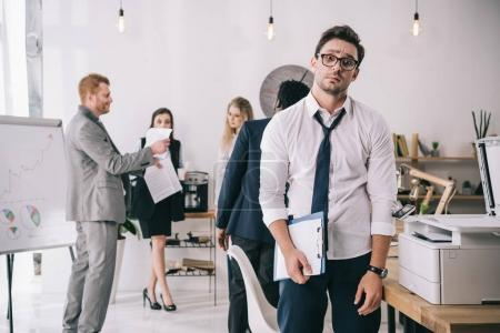 bewildered overworked businessman standing in office with blurred colleagues working on background