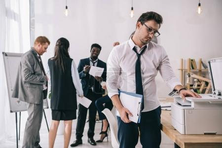 young handsome businessman using copier at office with blurred colleagues on background