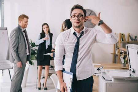 exhausted young manager making handgun gesture at office and looking at camera