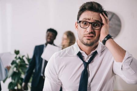 Photo pour Éperdu de jeune homme d'affaires touchant la tête et regardant la caméra au bureau - image libre de droit