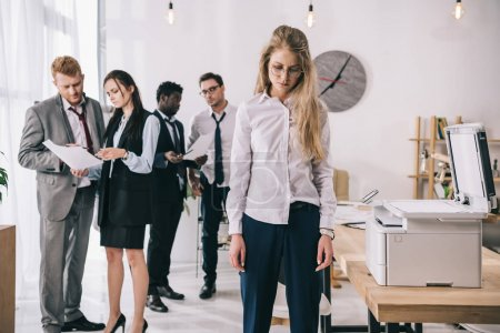 exhausted businesswoman standing near copier with colleagues working on background at office
