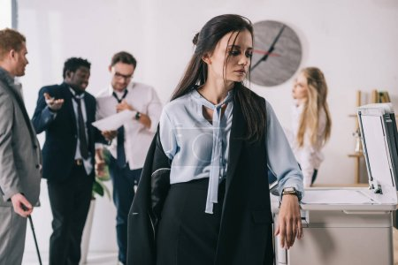 overworked untidy businesswoman standing near copier with blurred colleagues working on background at office