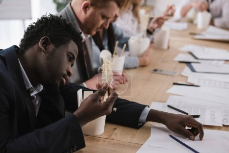 exhausted african american businessman eating noodles with his colleagues at office