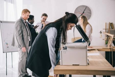 exhausted sleepy businesswoman leaning on copier at office while colleagues having conversation