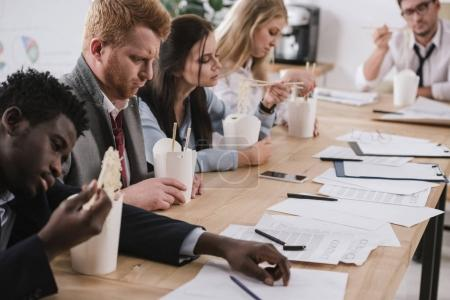 exhausted businesspeople eating noodles while having paperwork at office