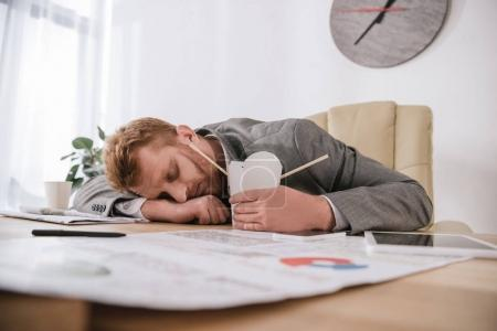 exhausted young businessman sleeping with box of take away noodles at workplace