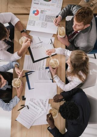 top view of businesspeople eating noodles while having paperwork at office